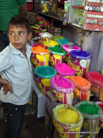 A minuscule vendor sells colored powders for Holi