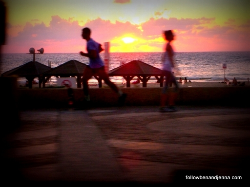 Sunset over the Mediterranean at Tel Aviv beach with joggers